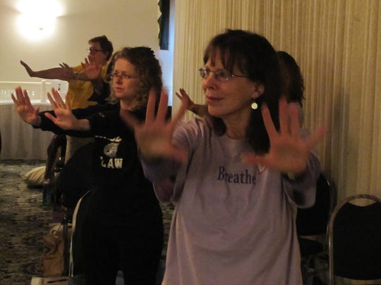 People attending the Breathe and Heal Conference at the Holiday Inn Express in Horseheads are led through motion and breathing exercises Friday by yoga instructor Joy Bennett.