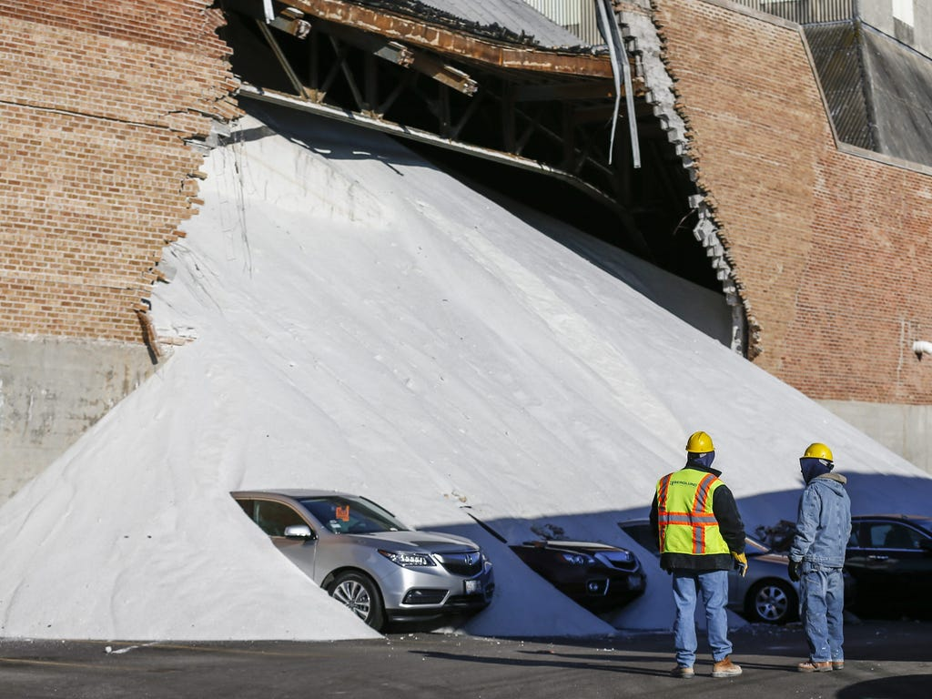 Workers inspect the result of s collapsed wall at the Morton Salt processing facility in Chicago that spilled tons of salt onto Acura automobiles parked on the adjacent car lot. The wall collapsed a day earlier.