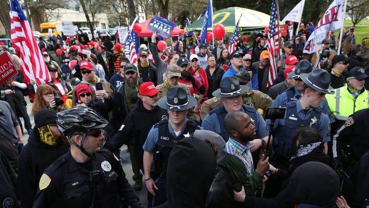 Salem Police officers intervene as pro-Donald Trump and anti-Trump protestors collide during dueling rallies on Saturday, March 25, 2017, at the Oregon State Capitol in Salem.