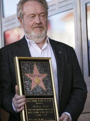 Ridley Scott poses with his star during the ceremony