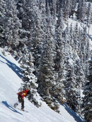 This undated photo provided by Taos Ski Valley shows a snowboarder headed down a steep trail at the resort in Taos. Taos Ski Valley is investing $300 million in the resort to update and expand its facilities. Improvements include a new lift to Kachina Peak, enhanced snowmaking, and modernized hotel, dining and shopping options.