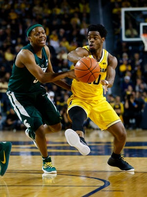 Michigan senior point guard Derrick Walton Jr., right, feeds a teammate with a pass past the defense of Michigan State Spartans freshman Cassius Winston Tuesday night in Ann Arbor.