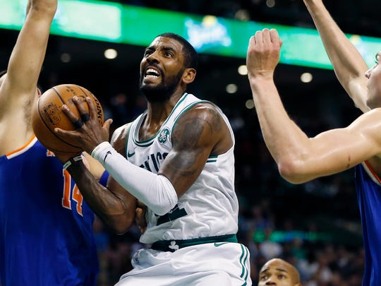 Boston Celtics' Kyrie Irving, center, drives for the basket between New York Knicks' Willy Hernangomez (14) and Kristaps Porzingis during the third quarter of an NBA basketball game in Boston, Tuesday, Oct. 24, 2017. The Celtics won 110-89.
