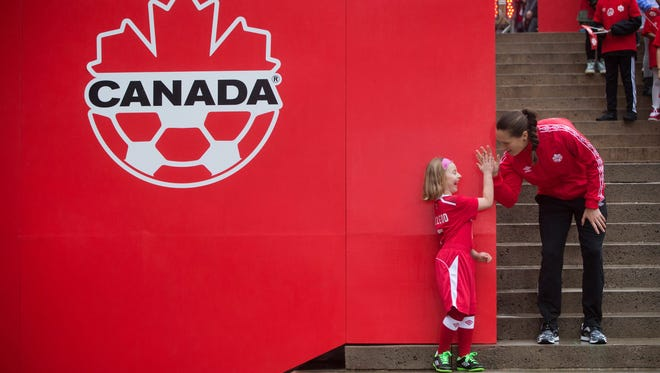 Canadian national women's soccer team goalie Erin McLeod, right, of St. Albert, Albrta, high-fives a young girl during the announcement of the roster for the 2015 FIFA Women's World Cup, in Vancouver, on April 27, 2015.