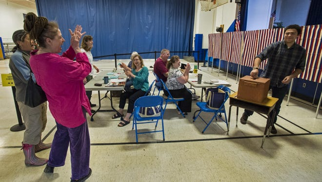 Sonam Friedensohn, right, gets a round of applause as he casts his first-ever ballot while voting on the school budget at the Westford Elementary School on Tuesday, May 5, 2015.