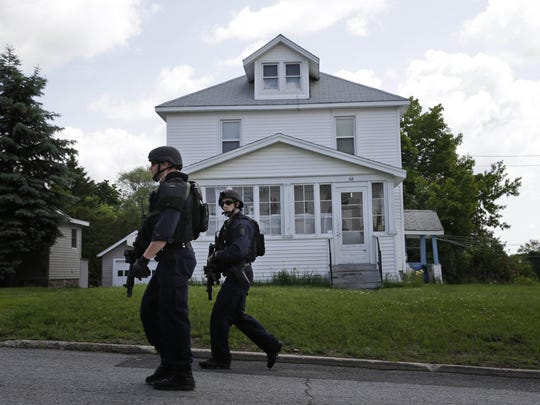 Law enforcement officers walk the streets near the prison in Dannemora, N.Y., as they searched houses near the maximum-security prison in northern New York where two killers escaped using power tools,Wednesday, June 10, 2015. State Police said the fifth day of searching will entail going from house to house in Dannemora, where David Sweat and Richard Matt cut their way out of the Clinton Correctional Facility.