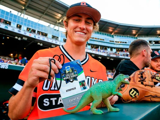 In this June 20, 2016 photo, Oklahoma State's Jacob Chappell displays at TD Ameritrade Park in Omaha, Neb., the official NCAA accreditation to the NCAA mens baseball College World Series for Utropolis, a plastic Tyrannosaurus rex that he and a good many of his teammates believe is the charm that has kept the wins coming. The palm-sized dinosaur joined the team after Chappell found him on a sidewalk in Oklahoma City during the Big 12 tournament. (AP Photo/Nati Harnik)