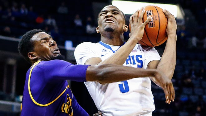 University of Memphis guard Jeremiah Martin (right) drives the lane against East Carolina University defender Caleb White (left) during first half action at the FedExForum.
