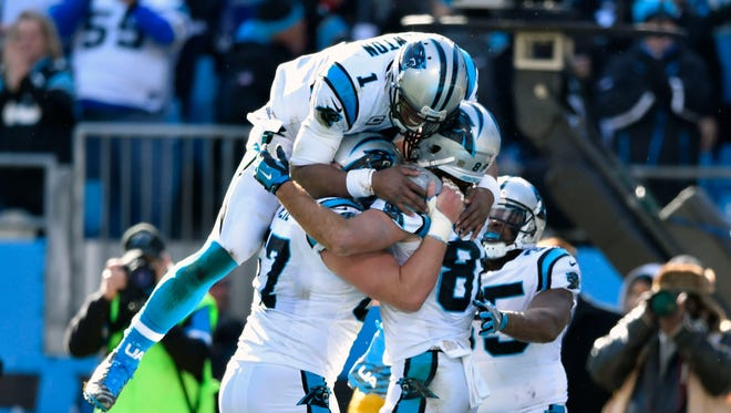 Carolina Panthers quarterback Cam Newton (1) celebrates his 19 yard touchdown pass to Greg Olsen (88) in the second quarter during the NFC Divisional round playoff game at Bank of America Stadium.