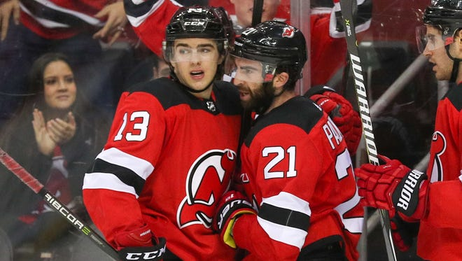 New Jersey Devils center Nico Hischier (13) and right wing Kyle Palmieri (21) celebrate Palmieri's goal during the second period of their game against the Winnipeg Jets at Prudential Center.