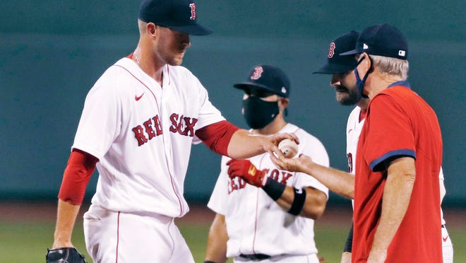 Red Sox reliever Jeffrey Springs, left, hands the baseball to manager Ron Roenicke as he is pulled after giving up a three-run homer to the Mets' Dominic Smith during the fourth inning Monday night.