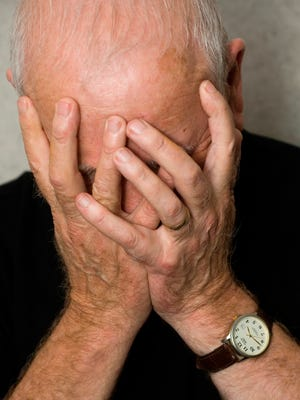 Old man covering face with hands in despair.