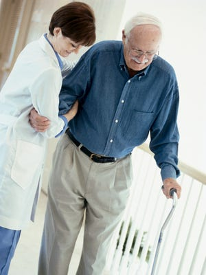 A doctor helping a patient to walk with a cane