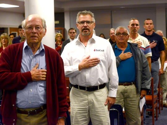 People stand and recite the Pledge of Allegiance on Tuesday at Pace High School during a Santa Rosa County Delegation meeting about proposed changes to a statute regarding the Pledge of Allegiance in the classroom.