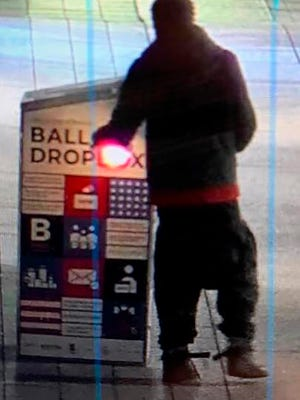 "This surveillance image provided by the Boston Police Department shows a man approaching a ballot drop box outside the Boston Public Library, early Sunday, Oct. 25, 2020, in downtown Boston. Massachusetts election officials say a fire was set at the ballot drop box holding more than 120 ballots in what appears to have been a ""deliberate attack."" Boston Police say that an arson investigation is underway and the person shown in this surveillance image is a person of interest."