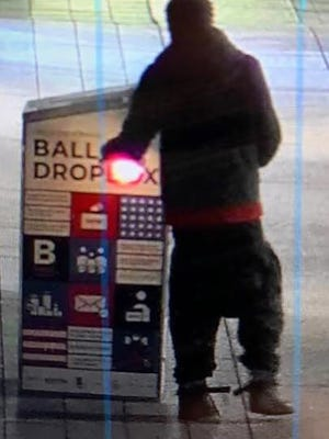 "This surveillance image provided by the Boston Police Department shows a man approaching a ballot drop box outside the Boston Public Library, early Sunday, Oct. 25, in downtown Boston. Massachusetts election officials say a fire was set at the ballot drop box holding more than 120 ballots in what appears to have been a ""deliberate attack."" Boston Police say that an arson investigation is underway and the person shown in this surveillance image is a person of interest."