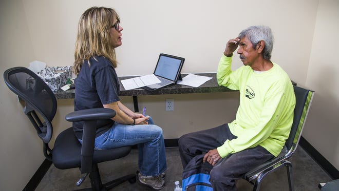 Intake specialist Tammy Pancoast interviews Phillip DeLeon, 62, inside the new Brian Garcia Welcome Center at the Human Services Campus in downtown Phoenix on March 15, 2017.