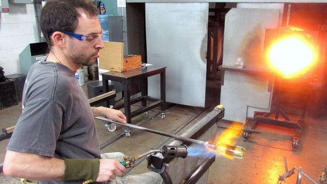 Local glass artist David Mirer fires up a piece in The Studio at the Corning Museum of Glass.