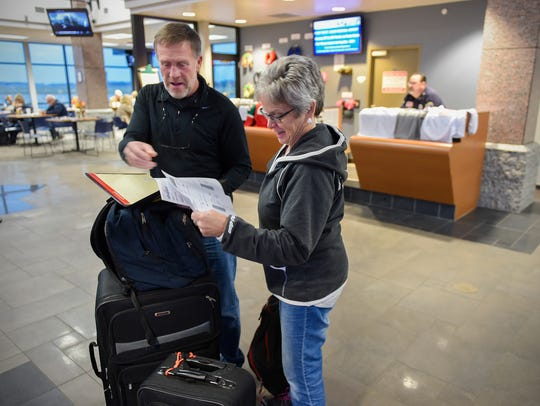 Randy and Jean Johnson pull out their boarding passes