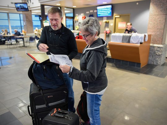 Randy and Jean Johnson pull out their boarding passes to check in for the first Allegiant flight to Punta Gorda, Fla. Wednesday, Nov. 15, at the St. Cloud Regional Airport.