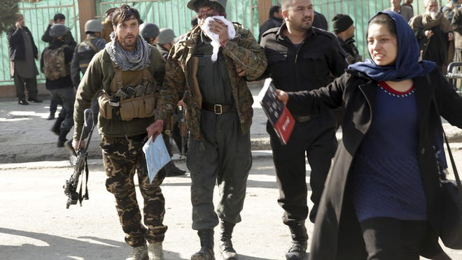 Wounded people are assisted at the site of a deadly suicide attack in the center of Kabul, Afghanistan, Saturday, Jan. 27, 2018. Afghan Public Health Ministry says dozens have been killed and over 100 wounded in suicide car bomb attack in capital Kabul. (AP Photo/Massoud Hossaini)
