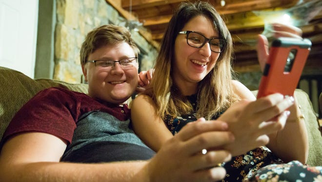 Zach Eason, 20, and Luz Skywalker, 21, look at a phone together while relaxing in entertainment room of Eason's home on Tuesday.