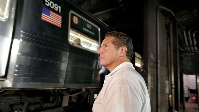 New York Gov. Andrew Cuomo from the track bed as subway train passes in the Columbus Circle station during a media tour in New York, Wednesday, Aug. 9, 2017.  Cuomo on Wednesday promised that the system's power provider, Con Edison, is now working with the Metropolitan Transportation Authority, which runs the subway system, on fixes and upgrades that will reduce delays substantially.