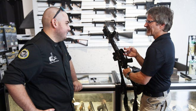William Andraca, 19, of Naples, left, talks with owner Jamie Knoop about accessories for his new AR-15 at Naples Gun Range and Emporium on Tuesday, June 21, 2016.