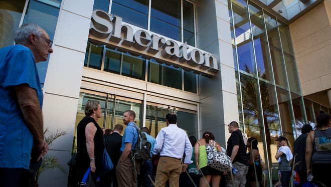 Displaced guests gather outside the east entrance to the Sheraton after a fire led to the evacuation of 800 occupants Oct. 25 in downtown Phoenix.