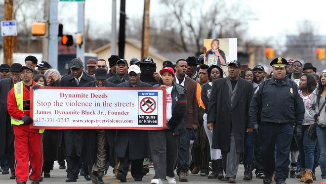"""IMPD Chief Rick Hite (right) leads marchers in a chant, """"Stop the violence, increase the peace,"""" during a walk from Pilgrim Baptist Church to the home in the 3100 block of North Harding Street where four people were killed Tuesday. The Ten Point Coalition brought together members of the community, as well as civic leaders, for the march through the Near-Northside neighborhood on Sunday, March 29, 2015."""