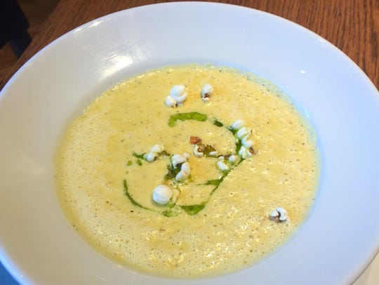 Sweet corn chowder with herbed oil and popcorn garnish.