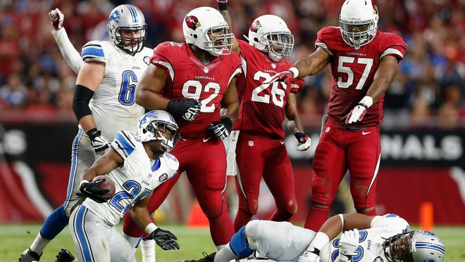 Nose tackle Dan Williams #92, free safety Rashad Johnson #26 and outside linebacker Alex Okafor #57 of the Arizona Cardinals celebrate after a defensive stop against running back Theo Riddick #25 of the Detroit Lions during the third quarter of the NFL game at the University of Phoenix Stadium on November 16, 2014 in Glendale, Arizona. The Cardinals defeated the Lions 14-6.