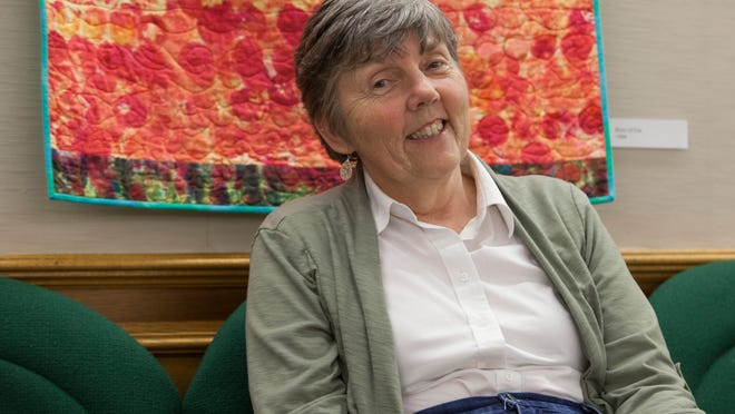 Barbara Moll sits in the large meeting room of the Minnetrista Building where her quilts are on display. Moll's work is also featured at the Indianapolis Museum of art.