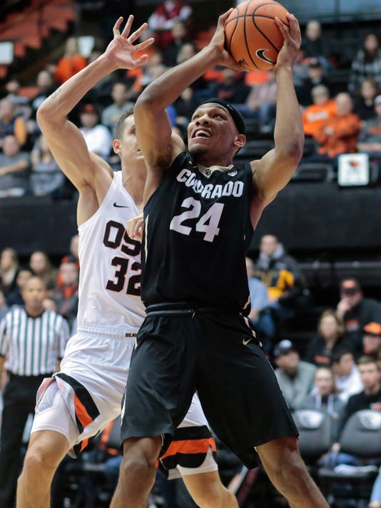 Colorado's George King (24) drives past Oregon State's Seth Berger (32) during the first half of an NCAA college basketball game in Corvallis, Ore., Friday, Dec. 29, 2017. (AP Photo/Timothy J. Gonzalez)