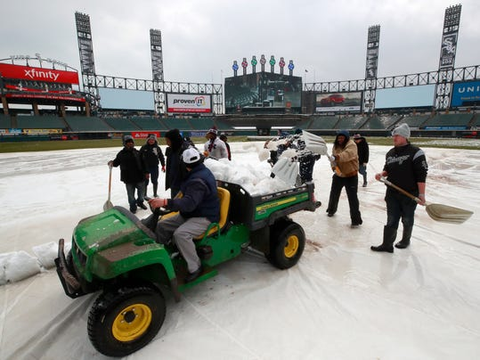 Grounds crew members remove snow from the field before a baseball game between the Chicago White Sox and the Tampa Bay Rays in Chicago, Monday, April 9, 2018. (AP Photo/Jeff Haynes)