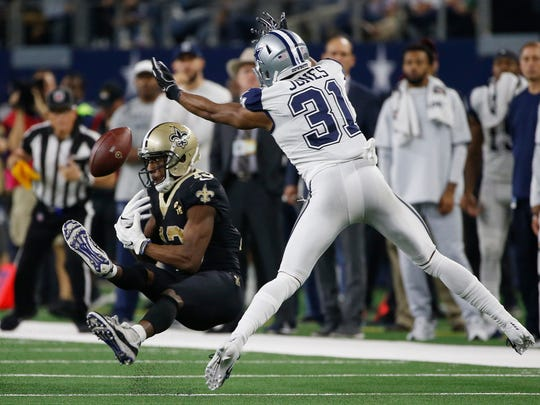 Dallas Cowboys cornerback Byron Jones (31) breaks up a pass intended for New Orleans Saints wide receiver Michael Thomas during a 2018 game in Arlington, Texas.