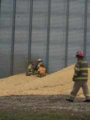 Workers cut a hole in the side of a grain bin near Murray in an attempt to rescue a man trapped Wednesday.