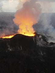 In this July 14, 2018 photo, lava from Kilauea volcano erupts in the Leilani Estates neighborhood near Pahoa, Hawaii.