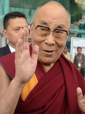 Tibetan spiritual leader, the Dalai Lama, gestures on his arrival at the airport in Amritsar on September 22, 2016.