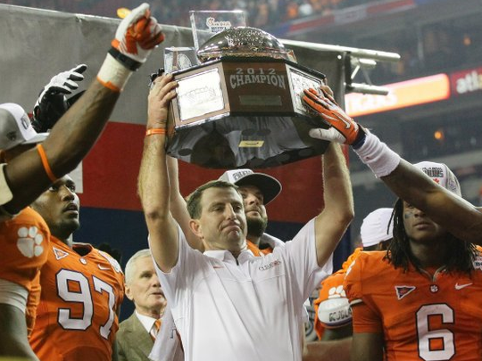 Clemson head coach Dabo Swinney holds up the trophy