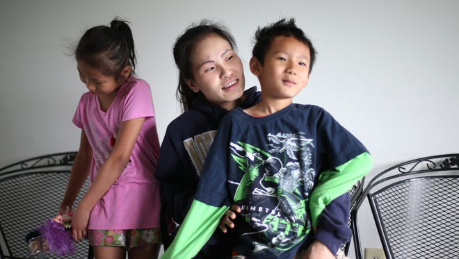 Mu Mu, a refugee of Myanmar (formerly Burma) plays with her 5-year-old son, Jobmu, and her 9-year-old daughter, Ju Aye Aye, from their modest apartment in Des Moines. Mu Mu became a single parent after her husband, Way Moo, committed suicide after being charged with child abuse after disciplining Jobmu earlier this year.