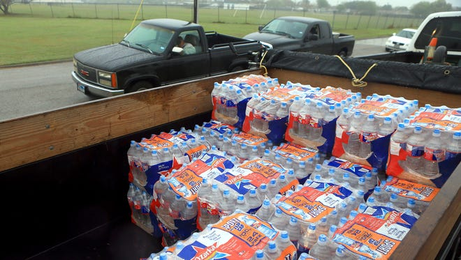 Cases of water sit in the back of a flat bed as volunteers prepare to hand out free water to vehicles Friday, Dec. 16, 2016, at Greenwood Senior Center in Corpus Christi. City officials confirmed Thursday morning that one chemical contaminated the city's water supply.