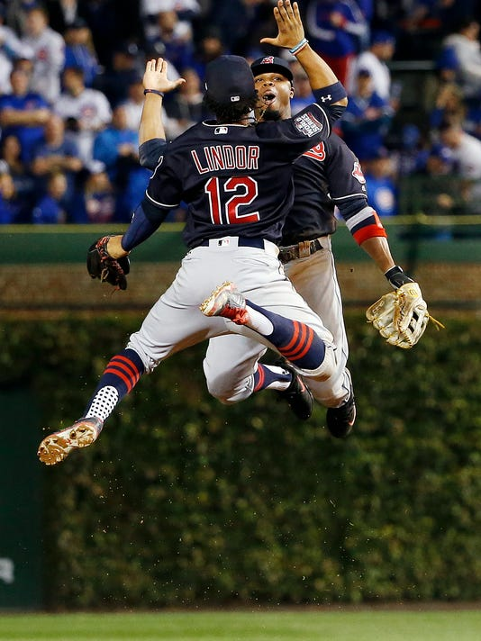 Cleveland Indians' Francisco Lindor (12) and Rajai Davis celebrate after Game 3 of the Major League Baseball World Series against the Chicago Cubs, Friday, Oct. 28, 2016, in Chicago. The Indians won 1-0 to take a 2-1 lead in the series. (AP Photo/Nam Y. Huh)