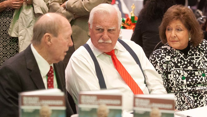 """Coach Howard Schnellenberger, center, and golf pro Buddy Demling, left, and Buddy's wife (and Howard's sister) Sara, right, chat as the former UofL football coach shows off his new book, """"Passing the Torch.""""05 November 2014"""