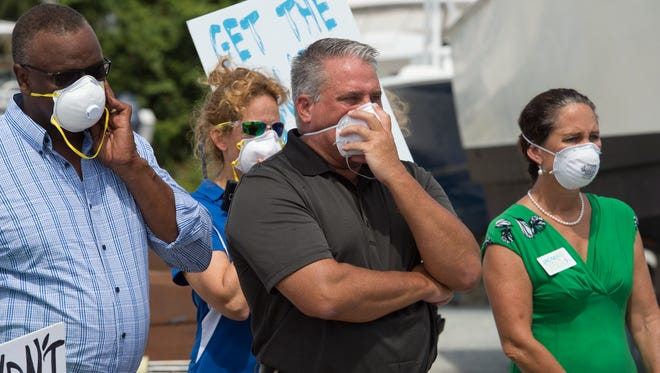 Protesters wearing protective masks listen to U.S. Rep. Patrick Murphy during his visit to Central Marine in Stuart on Sunday, July 10, 2016. The visit came in the midst of last summer's toxic blue-green algae blooms. A report released Wednesday by the American Civil Liberties Union says Florida officials did a poor job warning residents about the potential health hazards caused by the bloom.