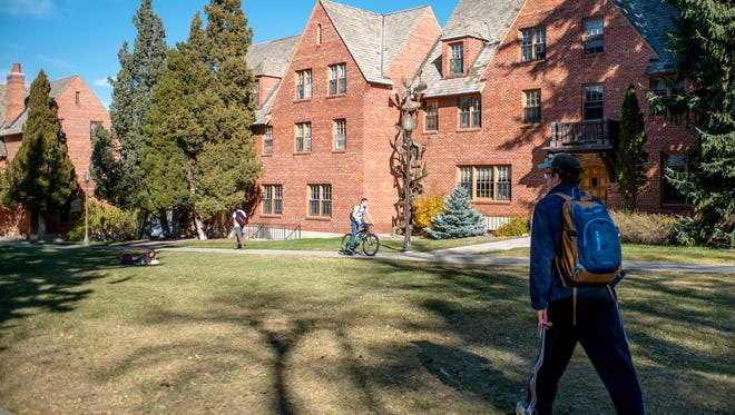 In this Thursday, Oct. 19, 2017 photo, students travel between classes outside of the Honors College on Montana State University campus. This year the Montana University System expects to offer tuition waivers and scholarships worth more than $48 million to more than 3,600 students statewide. The dollar total has grown nearly $8 million in the last five years. Montana State University, the state's largest and fastest growing campus, awards the most free tuition.  (Rachel Leathe /Bozeman Daily Chronicle via AP)