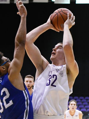 Furman's Matt Rafferty (32) scores over a UNC Asheville defender during a 2016 game.