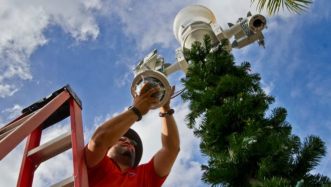 Tomas Duran, a technician with Integrated Fire and Security Solutions, install one of the surveillance cameras on First Street in Downtown Fort Myers, Wednesday afternoon (12/23/15).