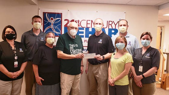 Lou Hoger accepts a check for $1,000 on behalf of the Perry Area Food Pantry from the staff of 21st Century Rehab at Dallas County Hospital. CONTRIBUTED PHOTO