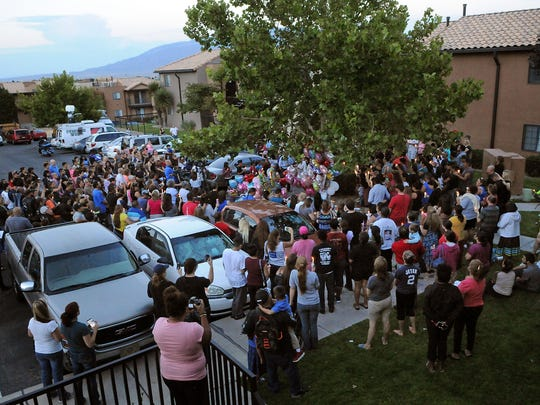 In this Thursday Aug. 25, 2016 photo, a couple hundred people attend a candlelight vigil for 10-year-old Victoria Martens at the apartment complex in Albuquerque, N.M., where the young girl lived and was killed. The mother of Victoria Martens told police she sought men online and at work to sexually assault her daughter before her death, according to warrants obtained by the Albuquerque Journal. Michelle Martens told police she had set up encounters with at least three men to sexual assault her daughter whose brutal death spark vigils and outcry across New Mexico.